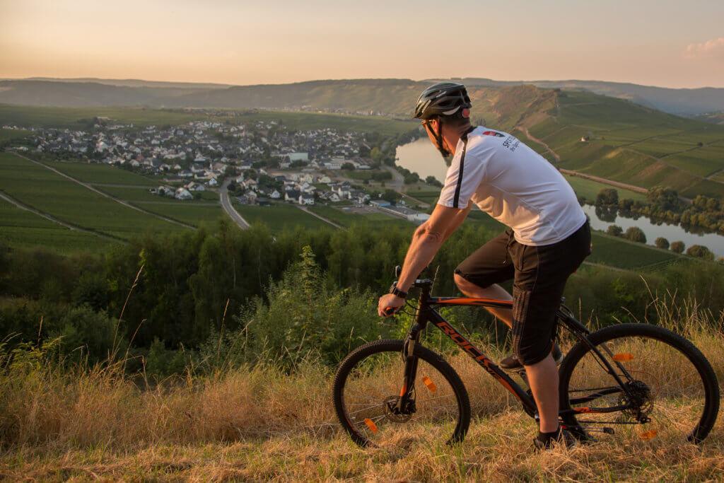 Fahrradfahrer auf einem Mountainbike, der auf einem Hügel steht undauf die Mosel schaut.