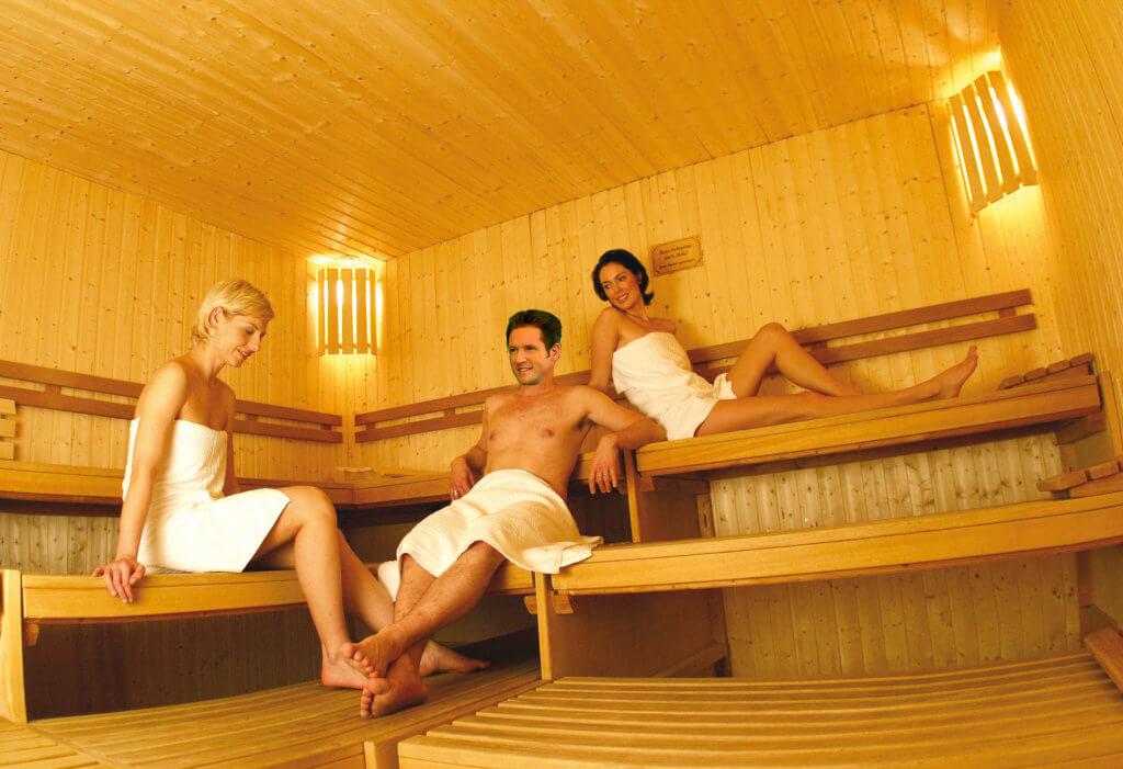 2 Frauen und ein Mann sitzen in der Sauna